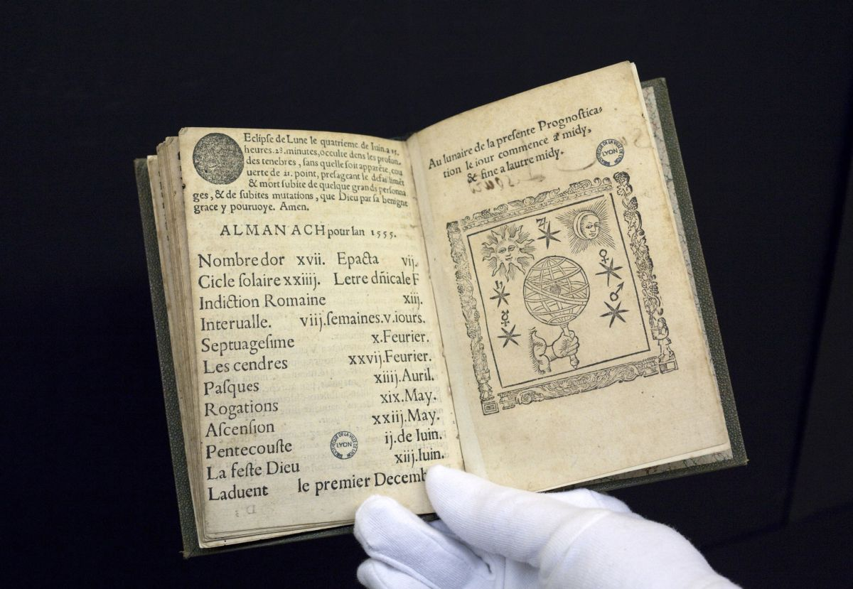 A 16th-century edition of predictions by Nostradamus, the first book to be digitised by Google from a collection of 500,000 at the Municipal Library of Lyon, is displayed by a librarian in this January 15, 2010 file picture. Amid the flat, wide fields of central France, a team of re-trained secretaries and IT experts is packaging Europe's literary heritage for the digital era. To match feature FRANCE-BOOKS/ REUTERS/Robert Pratta/Files (FRANCE - Tags: SCI TECH SOCIETY) - RTR297PK